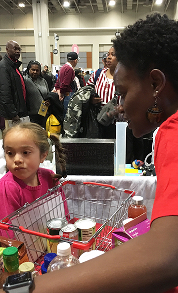 An ASM volunteer discusses microbes found in our food with a young festival attendee.