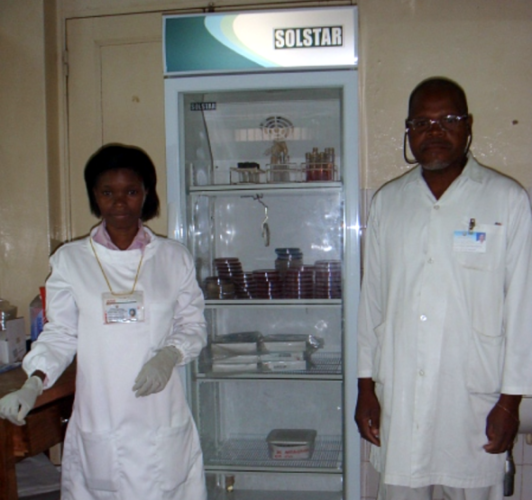 Laboratory staff pose in front of an incubator unit.